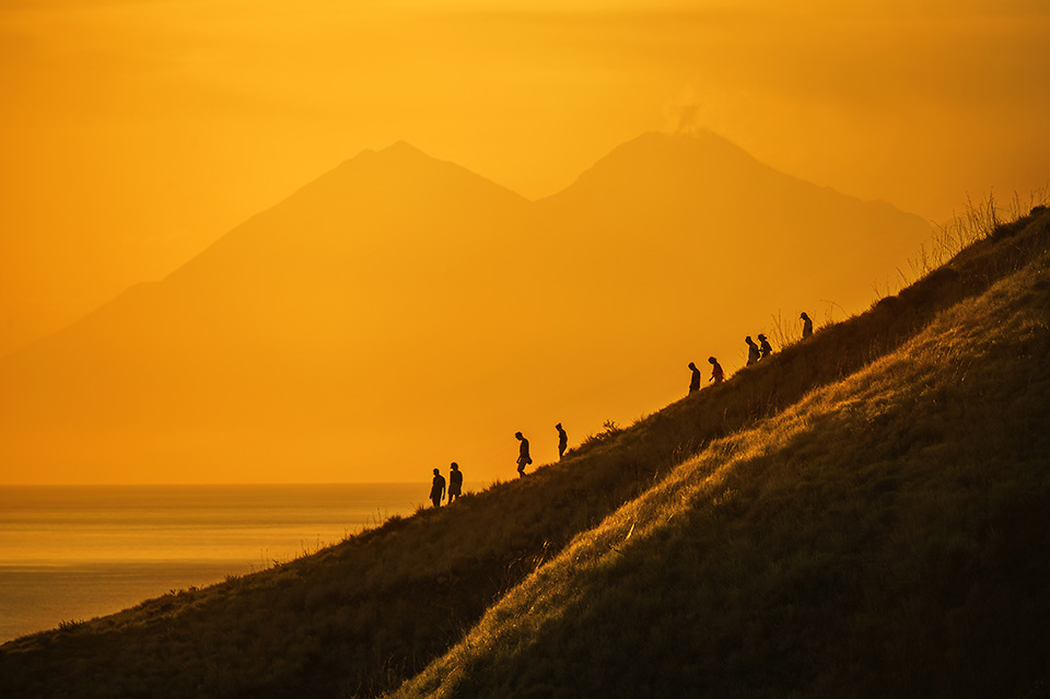 tourists-hiking-down-a-hill-at-sunset-komodo-island-indonesia