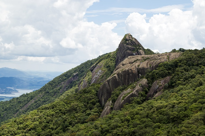 horizontal-view-of-a-mountain-rock-face-with-some-trees-under-a-blue-sky-with-white-clouds-pico-e-serra-do-lopo